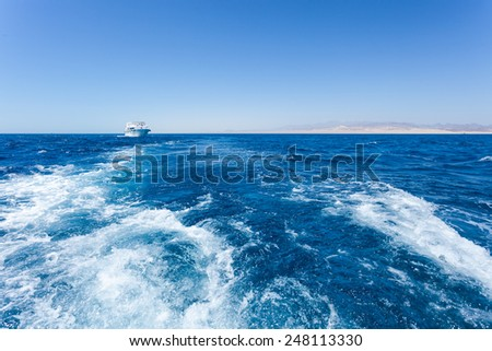 Water foam trace behind boat - stock photo