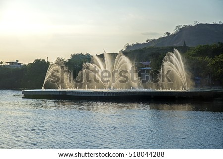 Water fountain and a lake in the city of Guayaquil, Ecuador, late afternoon.