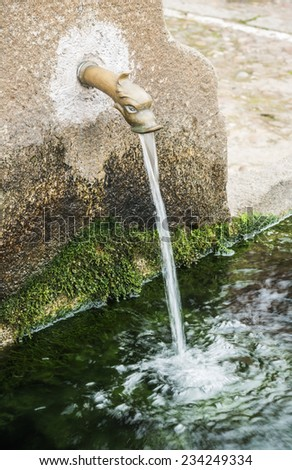 water fountain built in granite with bronze spout - stock photo