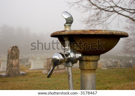 water fountain in a foggy cemetery