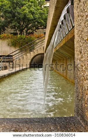 Water Fountain pouring into concrete pool - stock photo