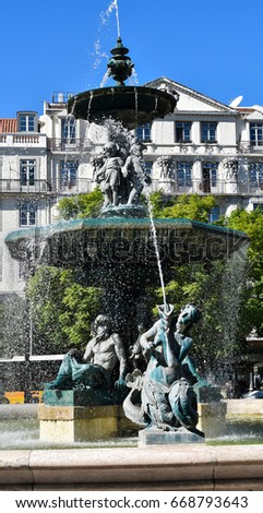 Water fountain with sculptures. Rossio square, Lisbon, Portugal.