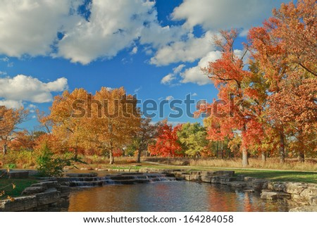 Water from Deer Lake at Forest Park cascades into a stream on an autumn day. - stock photo