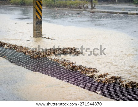 Water from heavy rain flows into a storm drain. - stock photo
