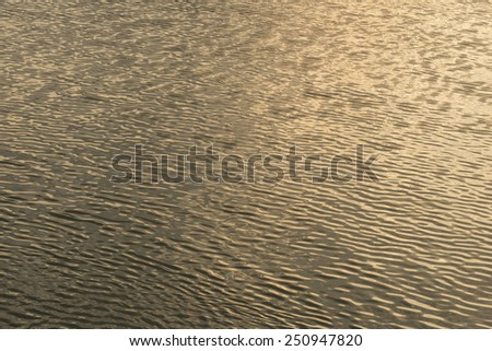 Water from lake reflecting golden sunlight from sun - stock photo