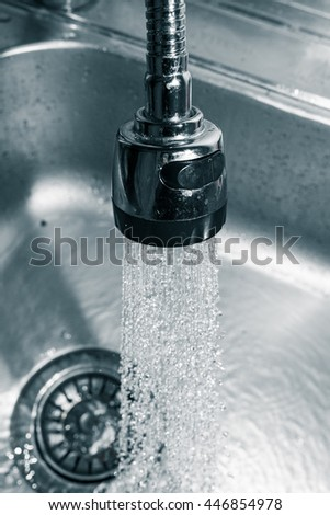 Water from the tap in the sink - stock photo