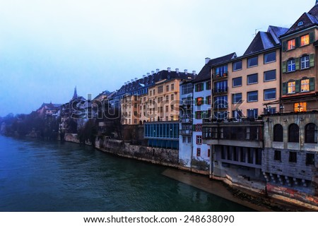 Water Front at the Rhine river in the Swiss City of Basel. Historical Buildings on a snowy and cold winter day in January - stock photo