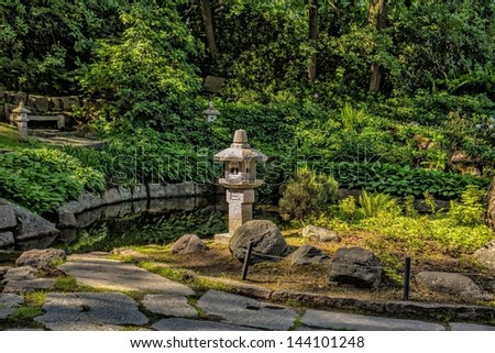 Water garden with cobblestone walkway and stone lanterns