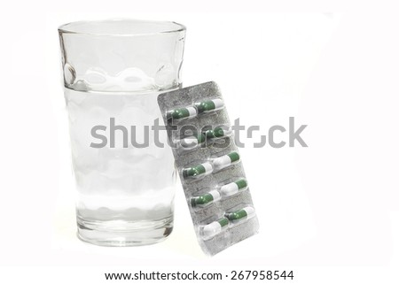 Water glass with capsules pills on white background. - stock photo