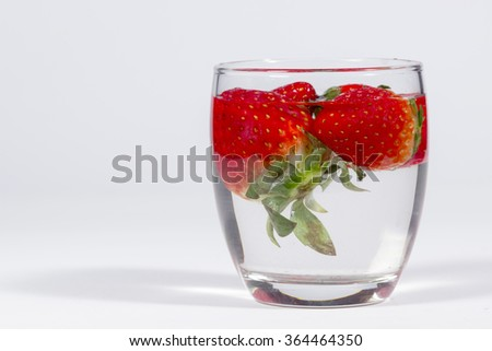 Water glass with floating strawberries, with blank space at left