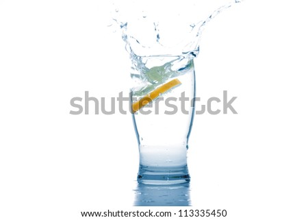 Water glass with liquid splash and lemon - stock photo