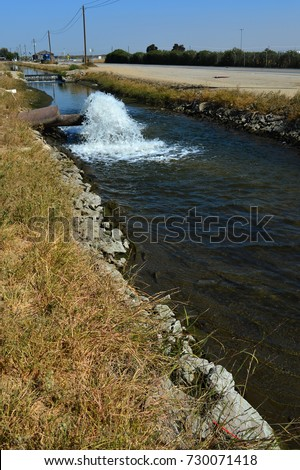 Water gushes from a pipe into a farm irrigation canal in Central California. The drought in prior years caused ground water to be pumped, lowering the water table.