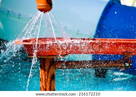 water gushing out of the hole of plastic pipe - stock photo