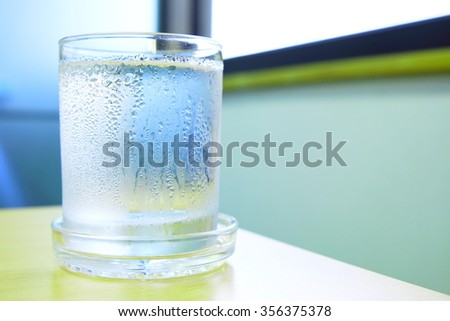 Water in a glass with water drops on wooden table, near the window. Selective focus on glass. Concept of blue-green tone. - stock photo
