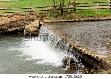 Water in a stream cascading over a small weir bordered by a paddock with a rustic wooden fence - stock photo
