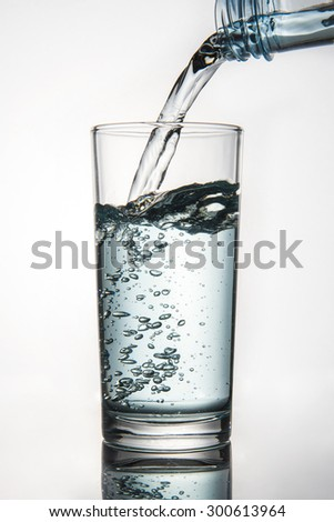 Water is pouring into the glass on white background