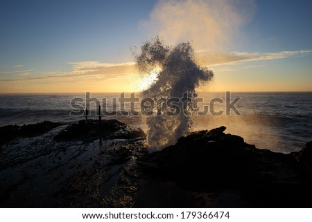 Water is shot up and out of a blowhole in the rocks in front of the early morning sunrise - stock photo
