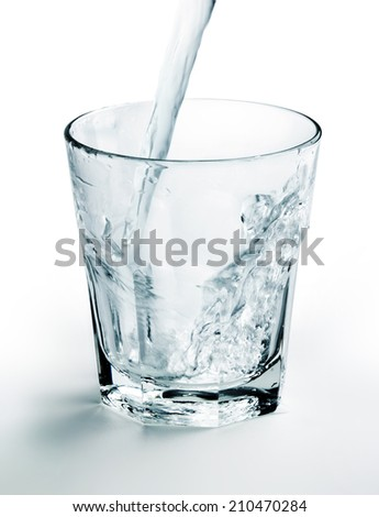 water jet filling a glass on white background