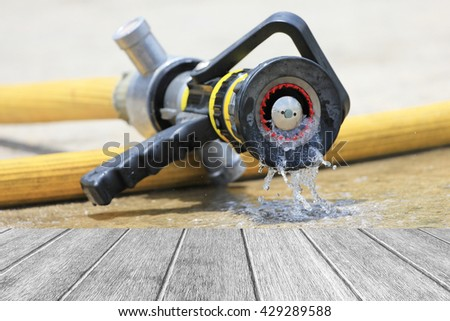 Water jet splashing from a fire fighting firehose nozzle - stock photo