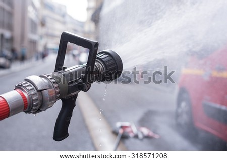 Water jet splashing from a fire fighting firehose nozzle with a red fire fighter truck in Paris - stock photo