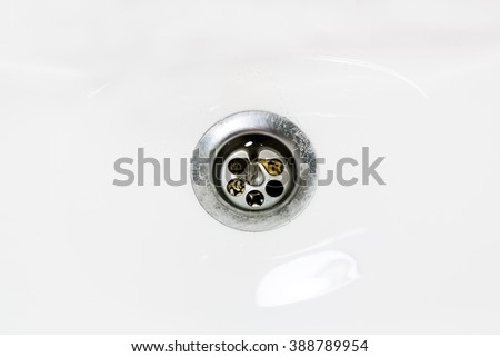 Water leaks in the drain hole in the sink - stock photo