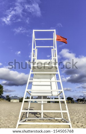 Water lifeguard stand with red flag - stock photo