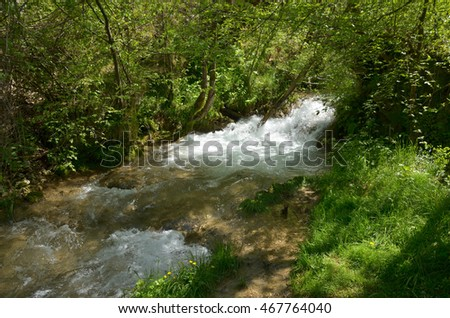 Water of a fast mountain river flowing down the mountain, creating overfalls and cascades