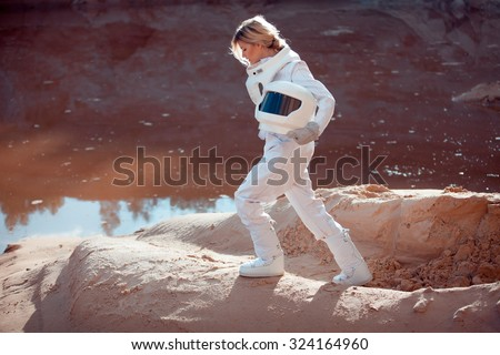 Water on Mars, futuristic astronaut without a helmet in another planet, image with the effect of toning - stock photo