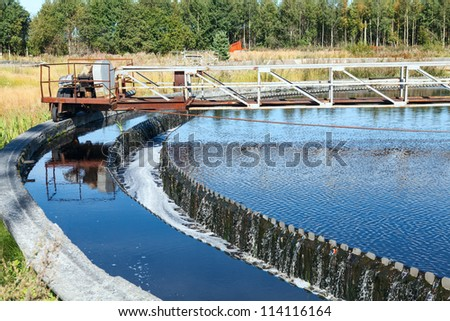Water overflow from the big sedimentation settler round form - stock photo