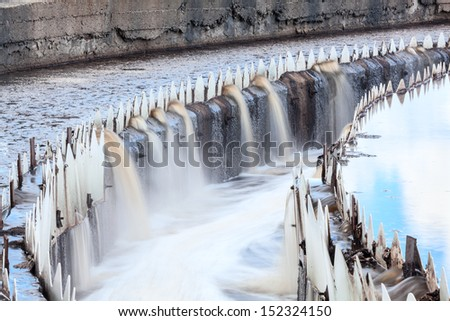 Water overflowing from round settlers, long exposure - stock photo