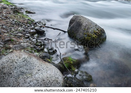 Water, photographed at a slower shutter speed, wraps around the stones that are in the river - stock photo