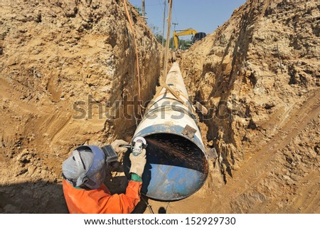 water pipes and worker on duty - stock photo