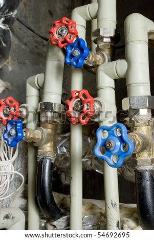 Water pipes with a valves of red and blue. - stock photo