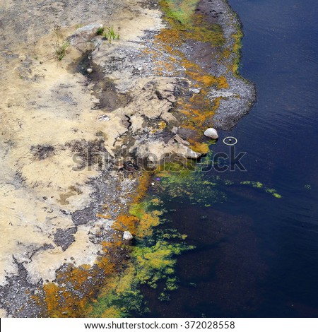 Water pollution in river. Dirty water stems from the pipe polluting the river. Global warming and pollution theme - stock photo