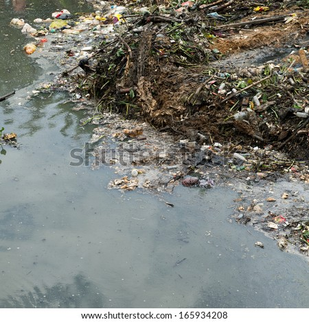 Water pollution in river with trash. - stock photo