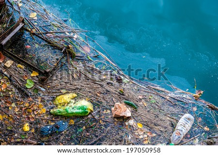 Water pollution old garbage and oil patches on river surface - stock photo