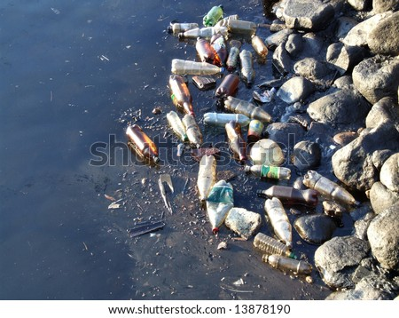 Water pollution - old garbage and oil patches on the surface. - stock photo