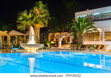 Water pool and fountain at night - vacation background - stock photo
