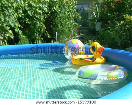 water-pool with toys in the garden - stock photo