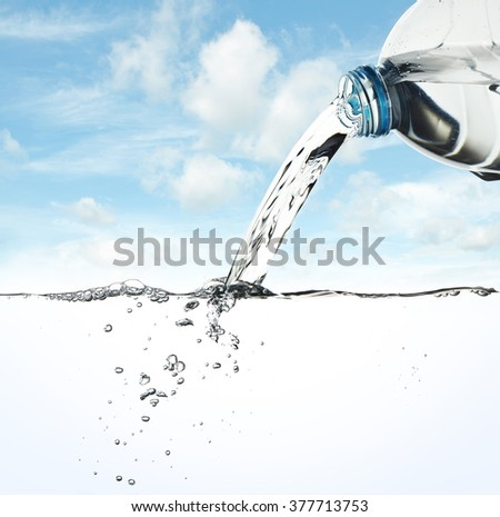 Water pour from water bottle on sky background