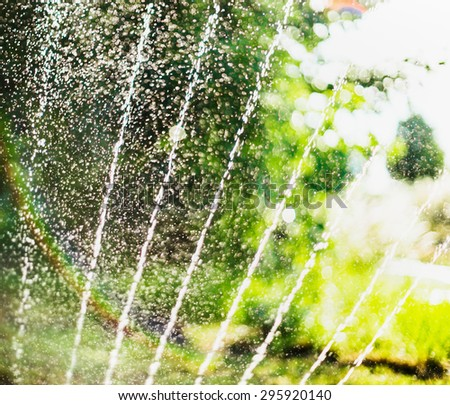 Water pour splashes and bokeh  from watering in summer garden with sprinkler on blurred tree foliage background - stock photo