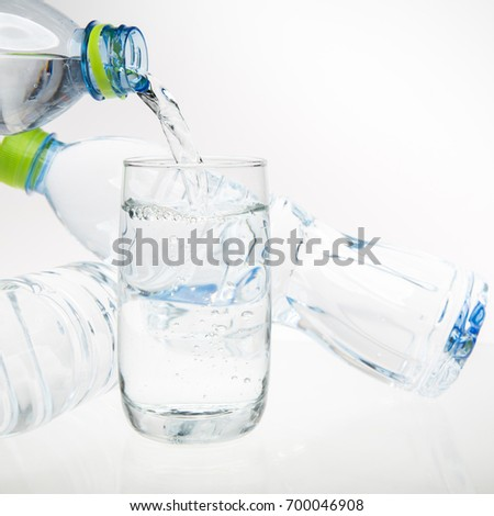 Water poured from a bottle into a glass on a white background