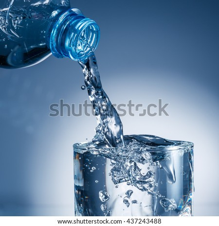 Water pouring from bottle into glass - stock photo