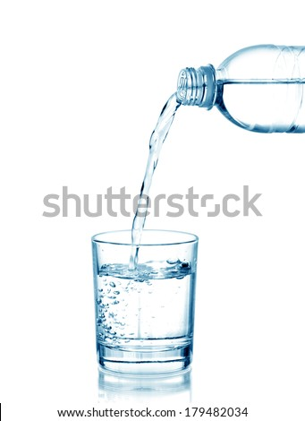 Water pouring from bottle into the glass, isolated on white - stock photo