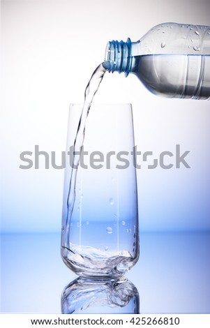 Water pouring from plastic bottle into empty drinking glass with reflection on white and blue background