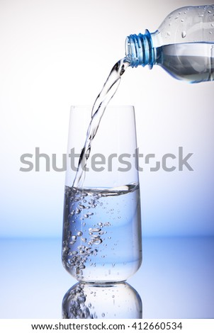 Water pouring from plastic bottle into half-filled drinking glass with reflection on white and blue background