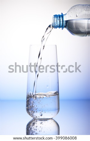 Water pouring from plastic bottle into one-third full drinking glass with reflection on white and blue background