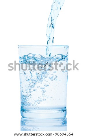 Water pouring into a glass, isolated on the white background, clipping path included. - stock photo