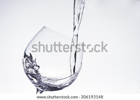 Water pouring into the wineglass - stock photo