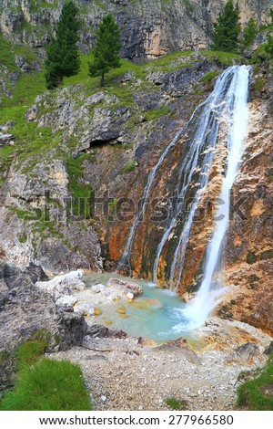 Water pouring over a cliff into small pond on Lasties valley, Sella massif, Dolomite Alps, Italy - stock photo